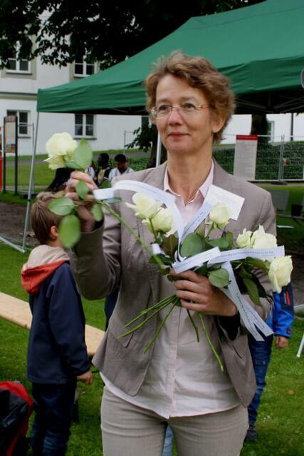 """Christl.-islam. Friedensgebet """"Willkommen, Mensch"""" am 20.06. Pfarrerin Ursula Leitz-Zeilinger, die am Ende Rosen mit der Aufschrift """"Es gibt keinen Weg zum Frieden, denn Frieden ist der Weg. Mahatma Gandhi"""" verteilt."""